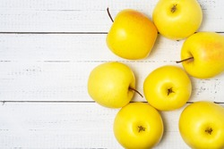 Heap of delicious yellow golden apples on white wooden table with copy space.