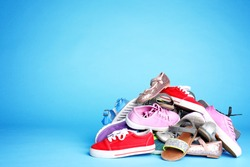 Heap of different shoes on color background. Space for text