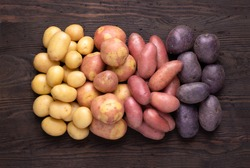 Heap of different types of potatoes on dark wooden rustic table