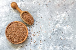 Heap of Flax seeds or linseeds in spoon or bowl on rustic background. Flaxseed concept, dietary fiber background
