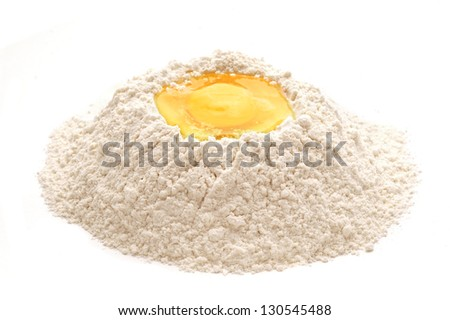 heap of flour with raw egg over white background