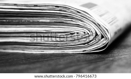 Heap of fresh morning newspapers on wooden table. Daily papers with news, articles, photos and headlines folded and stacked in pile. Stack of pages with selective focus, blurred background texture #796416673
