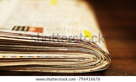 Heap of fresh morning newspapers on wooden table. Daily papers with news, articles, photos and headlines folded and stacked in pile. Stack of pages with selective focus, blurred background texture #796416676