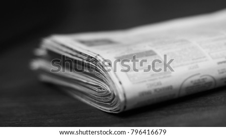 Heap of fresh morning newspapers on wooden table. Daily papers with news, articles, photos and headlines folded and stacked in pile. Stack of pages with selective focus, blurred background texture #796416679