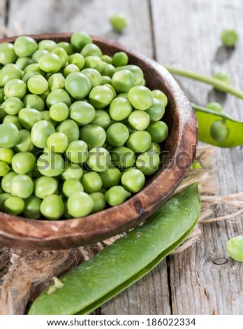 Heap of fresh Peas on wooden background (close-up shot)