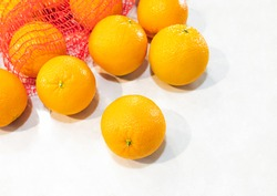 Heap of fresh quality selection orange from red net bag lay on white table background. Tropical juicy refreshment and healthy fruit, full of vitamin c and fiber. Natural sweet and tasty of all seasons