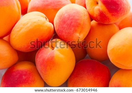 Heap of fresh ripe apricots on a white stone background. Close up. #673014946