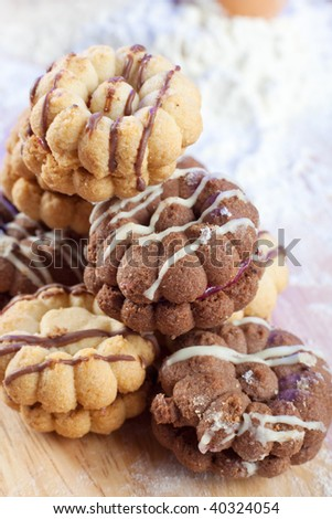 Heap of freshly made cookies on wooden bread board with some flour on the background
