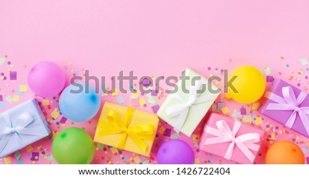 Heap of gift or present boxes, colorful balloons and confetti on pink pastel table top view. Birthday party background. Banner format.