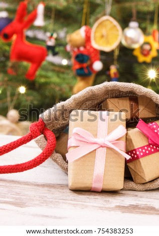 heap of gifts with ribbons in jute bag for christmas on background of christmas tree with