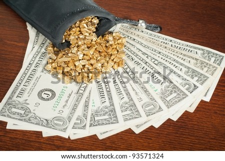 Heap of gold poured on banknotes.