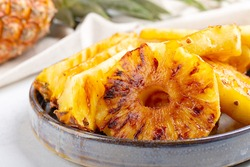 Heap of grilled pineapple slices on gray plate on concrete background.