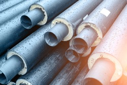 Heap of many new black insulated steel pipes at municipal construction site outdoors. Heating main district pipeline renewal or reconstruction. City development building industrial background