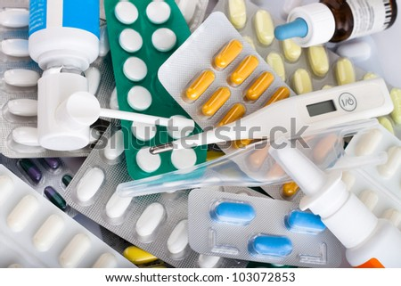 Heap of medical supplies, pills, tablets, capsules, nose drops and thermometer.