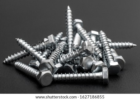 Heap of metal hex screws on black.