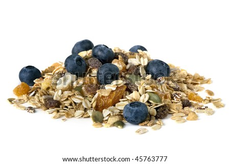 Heap of muesli with fresh blueberries, isolated on white.  Delicious granola cereal mix, with dried fruit and seeds.
