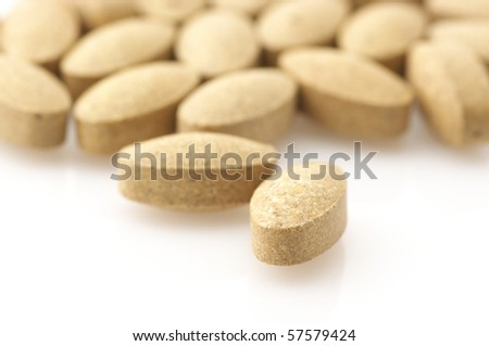Heap of nutritional supplement pills on white background.