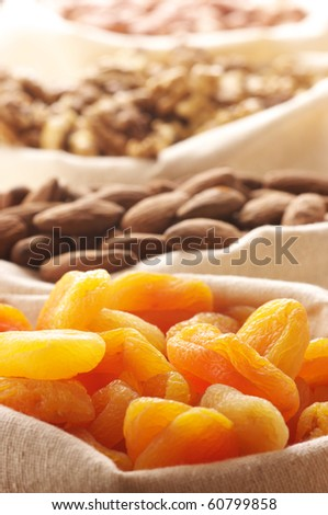 Heap of nuts and dried apricots in canvas bags. Focus on apricots.
