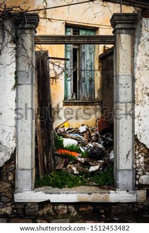 Heap of obsolete waste outside ruined house #1512453482