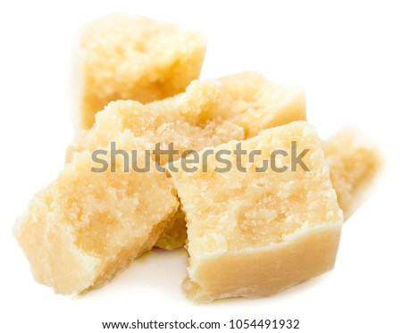 Heap of parmesan cheese pieces isolated on white background, close up