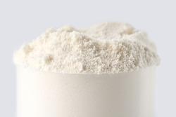 Heap of protein powder on white background. Scoops Of Protein Powder. Measuring spoon and heap of vanilla protein powder.