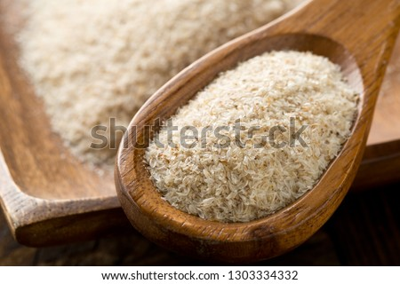 Heap of psyllium husk in wooden spoon and bowl on table. Psyllium husk also called isabgol is fiber derived from the seeds of Plantago ovata plant found in India. Selective focus. Stock photo ©
