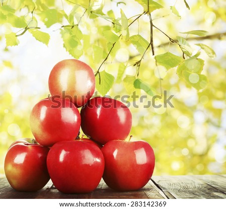 Heap of red apples on wooden table on nature background #283142369