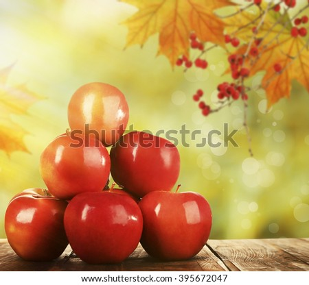 Heap of red apples on wooden table on nature background #395672047