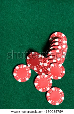 Heap of red poker chips on the green table. Symbol of risky entertainment
