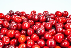 Heap of ripe red sweet cherries on a white background.
