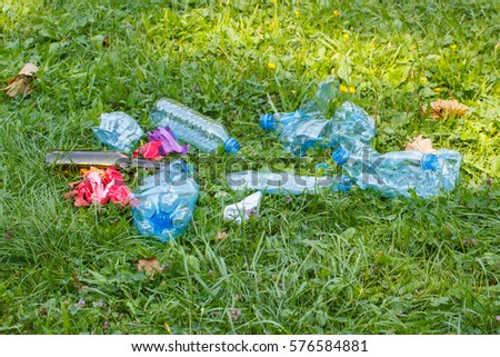 Heap of rubbish on grass in sunny park, plastic and glass bottles, bottle caps and paper, concept of environmental protection, littering of environment