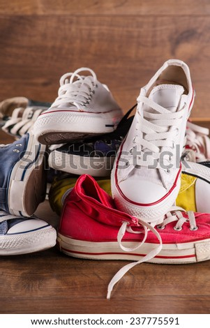heap of several  pairs of cool youth red blue white yellow  gym shoes   on brown wooden floor