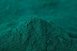 Heap of spirulina algae powder on a blurred background. Superfood concept. Macro photography.