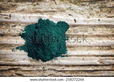 heap of spirulina algae powder on wooden background, top view