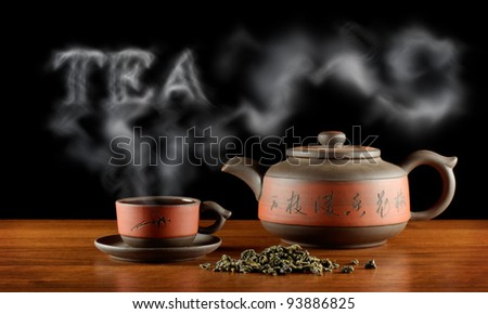 heap of tea, kettle and cup with hot tea and word \