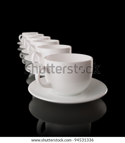 Heap of the white cups and saucers, isolated on black