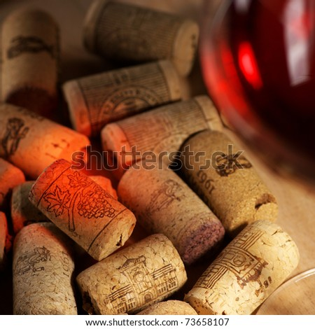 Heap of used vintage corks with glass of red wine and reflex. Selective focus on corks.