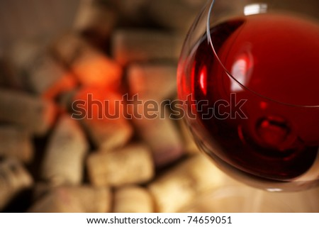 Heap of used vintage corks with glass of red wine and reflex. Selective focus on glass.