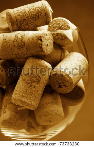 Heap of used vintage wine corks in wineglass close-up. Toned image.