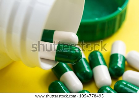Heap of white and green capsules on yellow table. Bottle spilling out tablets.