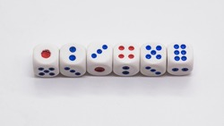Heap of white cubic tree six dices with blue and red spikes (dots) on a white background. Game, gambling, chance and risk concept