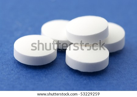 Heap of white pills close-up on blue background.