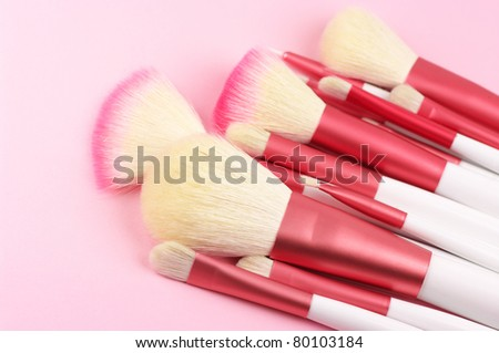 Heap of white-pink make-up brushes close-up on pink background. - stock photo