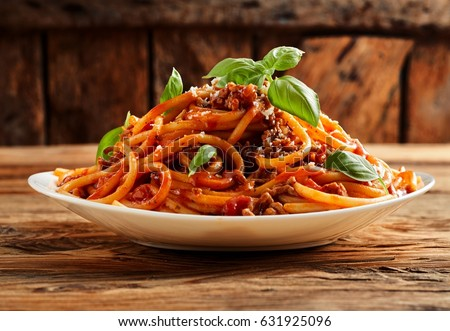 Heaped plate of delicious Italian spaghetti pasta with fresh basil leaves and grated parmesan cheese viewed low angle from the side on a rustic wood table #631925096