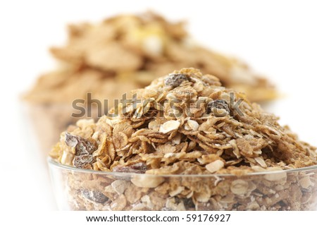 Heaps of breakfast cereals close-up in glass bowls on white background.
