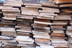 Heaps of natural wood planks in a building factory.