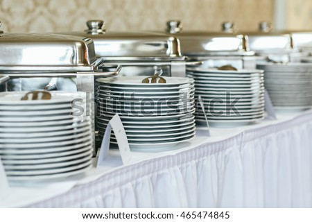 Heaps of white plates stand on the white buffet