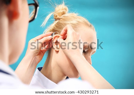 Hearing aid. The doctor assumes the woman hearing aid in your ear