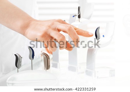 Hearing aids.\ Man shows a finger on a model hearing aid
