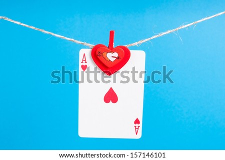 heart ace with clothes peg rope over blue background